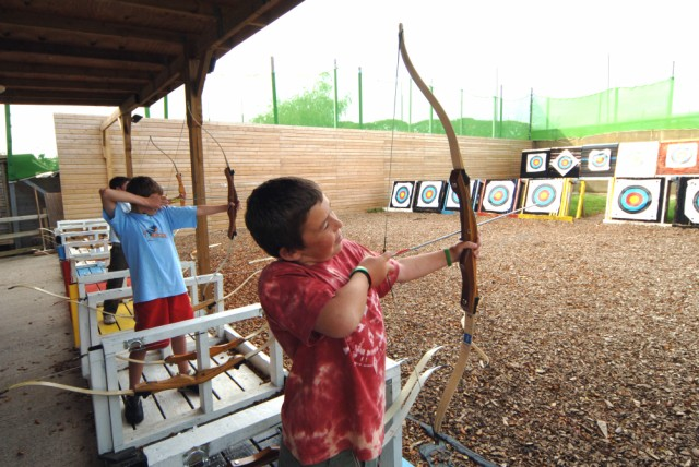 A kid shooting with an Archery Finger Tab.